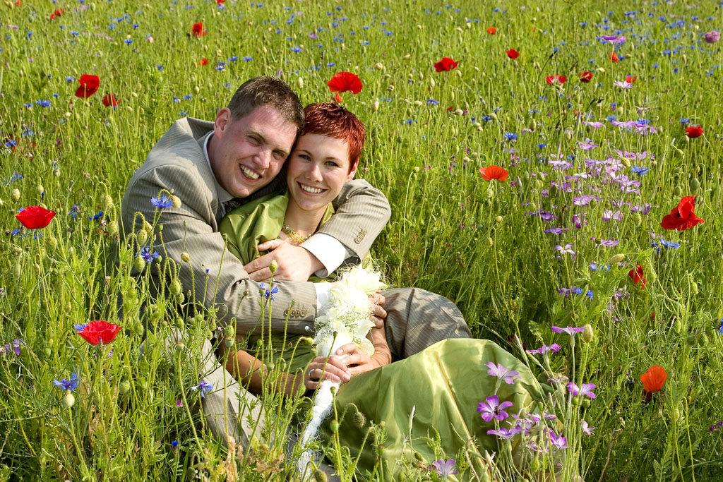 trouw-3:: Een bruidegom knuffelt zijn bruid in een wilde bloemenveld bij Zelhem